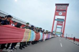 Kain Jumputan 1,1 Kilometer Membentang di Jembatan Ampera