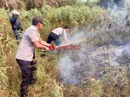 Polisi Padamkan Api dengan Ranting Kayu