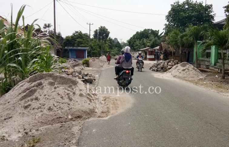 LAMPUNG POST   Tumpukan Material Pembangunan Drainase di Palasaji Bahayakan Pengguna Jalan